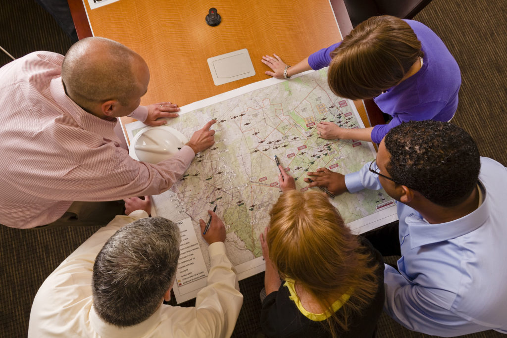 group of people at business meeting working over a map